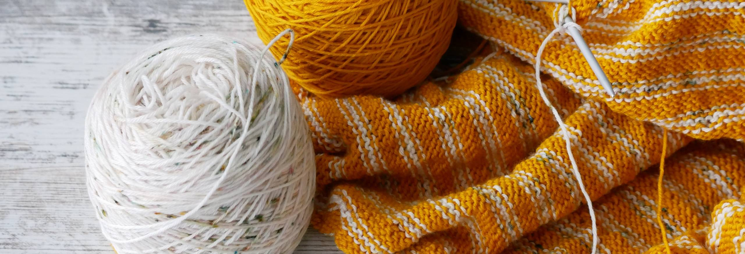 Golden Yellow and White Speckled yarn sits next to a striped knitting project