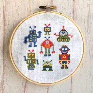 Robots cross-stitch on white aida cloth